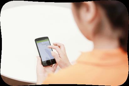 ヘルパーがスマートフォンでスマケアを閲覧している様子 イメージ写真